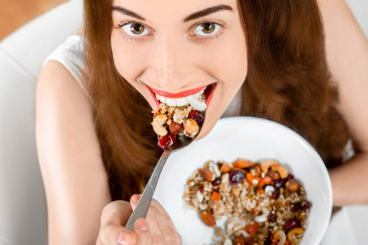 Young positive woman eating granola breakfast on the couch at home. Up-view