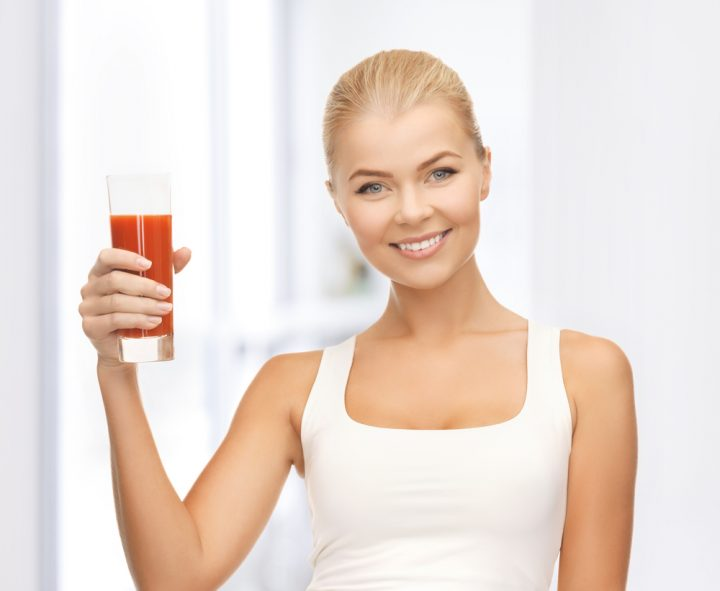 young woman holding glass of tomato juice