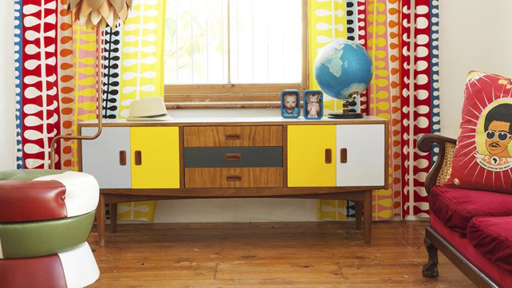 Renovated fifties sideboard below window with colourful, patterned curtains