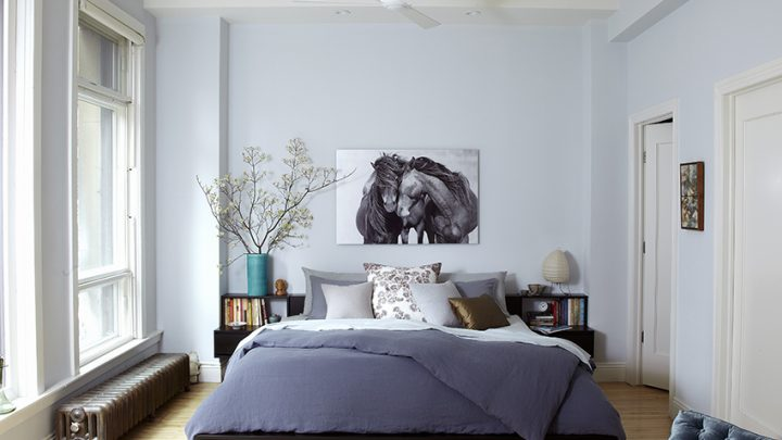 A King Size Bed in a Loft Bedroom with a Print of Horses Above the Bed