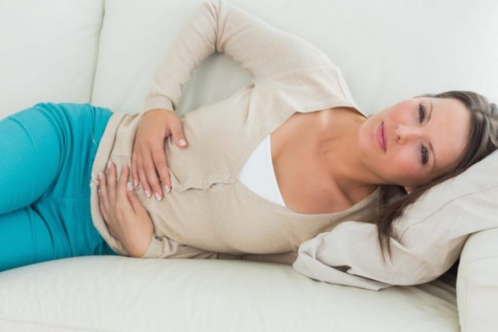 Woman lying on the sofa in the living room with upset stomach